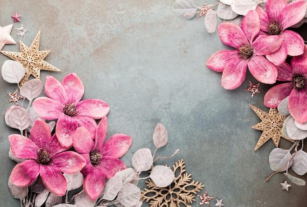 Празднование нового года и рождественский фон с розовыми цветами, снегом, звездами и рождественскими украшениями.