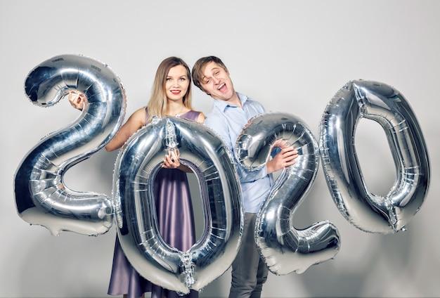 Новый год, праздник и концепция праздников - влюбленная пара весело со знаком 2020 из серебряных шаров на новый год