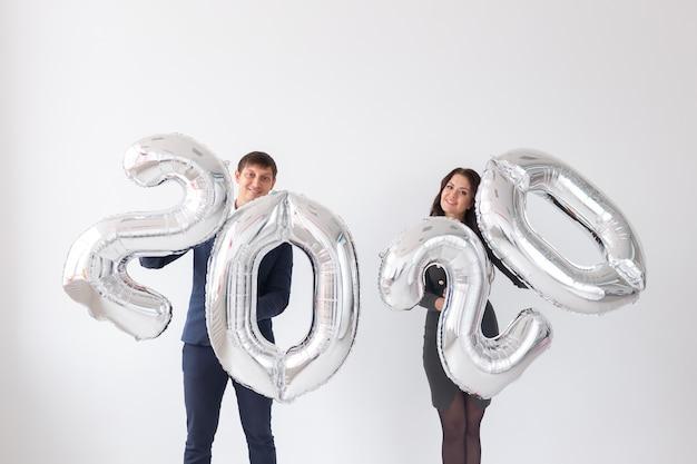 新年、お祝い、休日のコンセプト-シルバー製のサイン2020を楽しんでいる愛のカップル