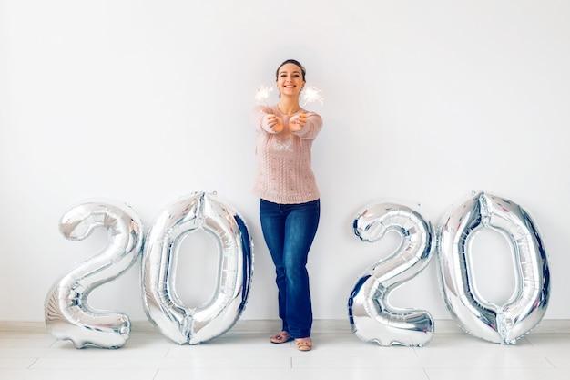 Празднование нового года и концепция партии - счастливая молодая женщина с бенгальские огни возле серебра 2020 воздушных шаров.