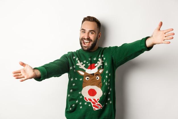 새 해 축 하 및 겨울 휴가 개념입니다. 친절한 남자는 포옹을 위해 손을 벌리고, 크리스마스 파티에 오신 것을 환영합니다, 재미있는 스웨터, 흰색 배경
