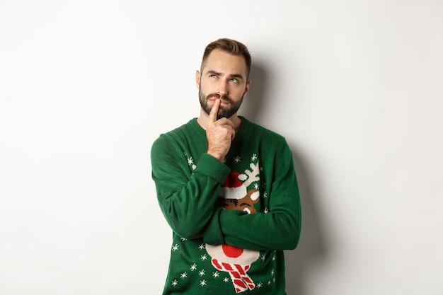 새 해 축 하 및 겨울 휴가 개념입니다. 수염을 기른 잘생긴 남자는 크리스마스를 계획하고, 왼쪽 상단 모서리를 생각하고 바라보며, 선물 아이디어, 흰색 배경을 생각합니다.