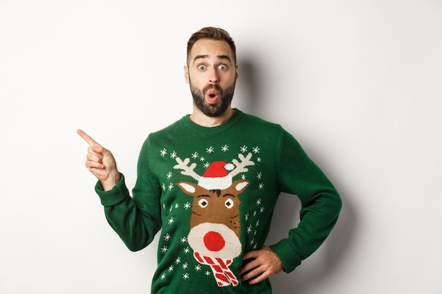 새 해 축 하 및 겨울 휴가 개념입니다. 크리스마스 스웨터를 입은 놀란 남자가 왼쪽 상단 모서리에 손가락을 가리키며 놀란 표정을 하고 흰색 배경