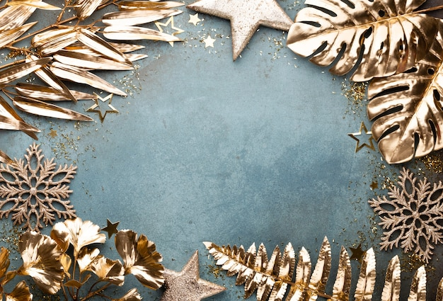 New year celebration and christmas background with golden flowers, snow, stars and christmas decorations top view.