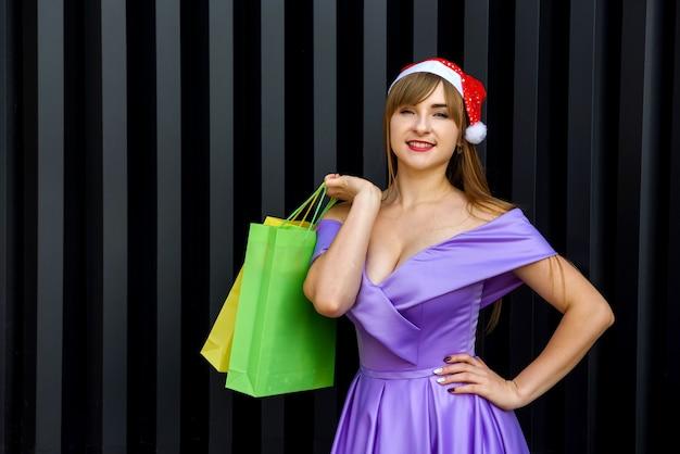 新年のお祝い。サンタの帽子のギフトカラフルなバッグとファッションイブニングドレスの幸せな女性
