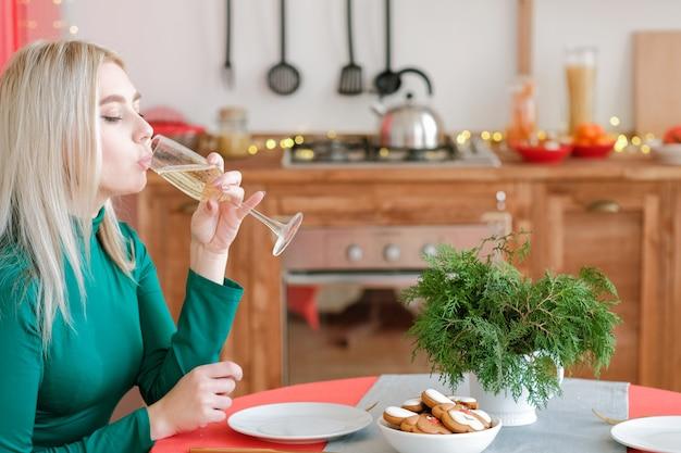 新年のお祝い。自宅のキッチンでシャンパンを飲む金髪の女性の側面図。
