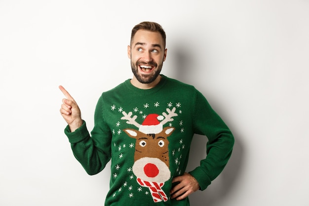 Celebrazione del nuovo anno e concetto di vacanze invernali. uomo barbuto da sogno con un maglione natalizio verde, che punta all'angolo in alto a sinistra e sorride divertito, sfondo bianco.