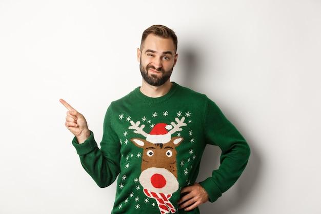 Celebrazione del nuovo anno e concetto di vacanze invernali. ragazzo scettico con un maglione natalizio che sembra dispiaciuto, puntando il dito sul prodotto nell'angolo in alto a sinistra, non mi piace, sfondo bianco