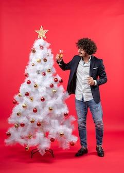 Celebrazione del nuovo anno con il giovane barbuto che tiene un bicchiere di vino e in piedi vicino all'albero di natale bianco decorato