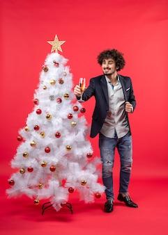 Celebrazione del nuovo anno con il giovane barbuto che tiene vino e in piedi vicino all'albero di natale bianco decorato
