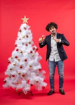 ひげを生やした若い男がワインを指して、装飾された白いクリスマスツリーの近くに立って新年のお祝い