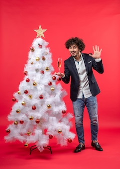 Celebrazione del nuovo anno con il giovane barbuto con vino che mostra cinque in piedi vicino all'albero di natale bianco decorato