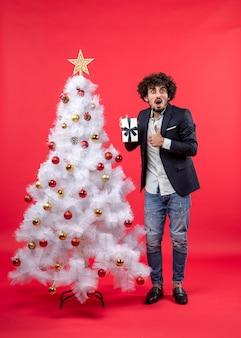 Celebrazione di nuovo anno con giovane scioccato che mostra il suo regalo che fa gesto giusto vicino all'albero di natale bianco decorato su metraggio rosso