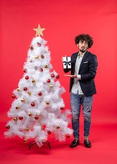 Celebrazione del nuovo anno con giovane scioccato che mostra il suo regalo vicino all'albero di natale bianco decorato su metraggio rosso
