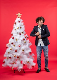 Celebrazione del nuovo anno con il giovane che nasconde qualcosa vicino all'albero di natale bianco decorato sul rosso