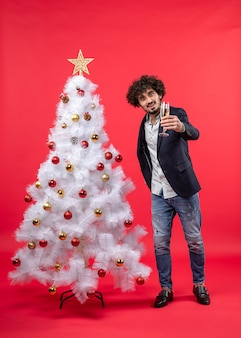赤い映像で飾られた白いクリスマスツリーの近くでワインのグラスを保持している若い男と新年のお祝い