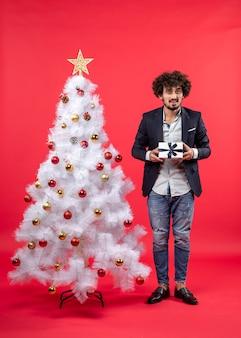 Celebrazione del nuovo anno con il giovane che tiene un regalo vicino all'albero di natale bianco decorato su metraggio rosso