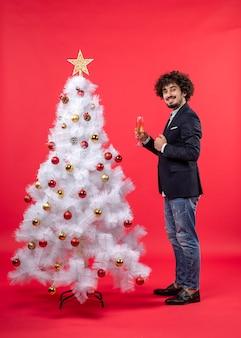 Celebrazione del nuovo anno con il giovane che tiene un bicchiere di vino vicino all'albero di natale bianco decorato sul rosso
