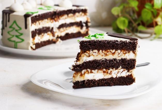 Новогодний шоколадный торт, кусочек на тарелке на свету