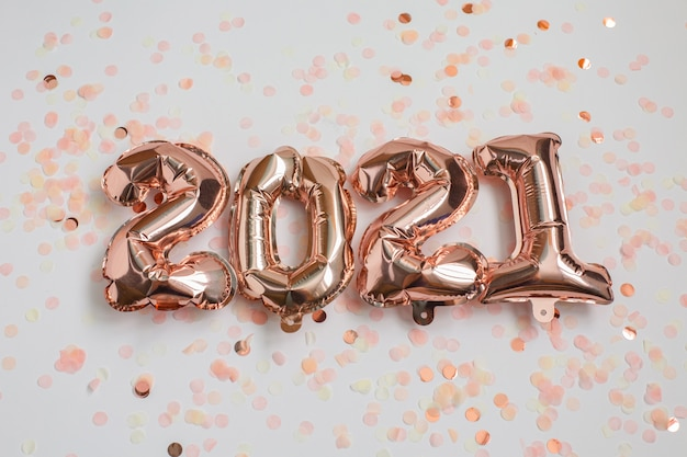 New year and christmas 2021 celebration concept. foil balloons in the form of numbers 2021 and confetti on pink background. air balloons. holiday party decoration.