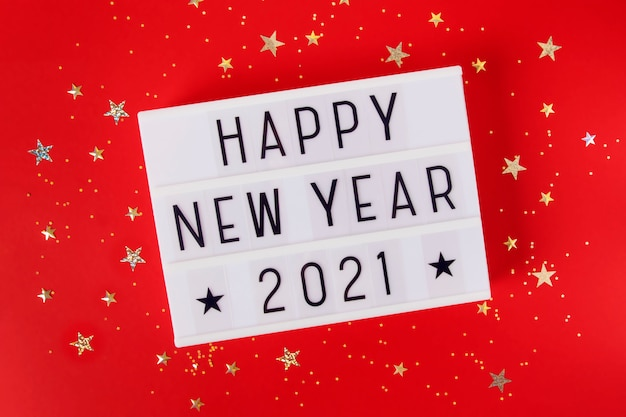 New year or christmas 2021 composition flat lay top view. xmas holiday celebration  lightbox with text red background. template for greeting card text design
