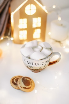 New year and christmas background with a cup of coffee with marshmallows and candles on white