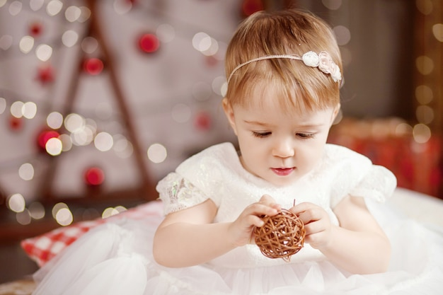 New year and christmas celebration concept. pretty little girl in white dress playing and being happy about christmas tree and lights. winter holidays.