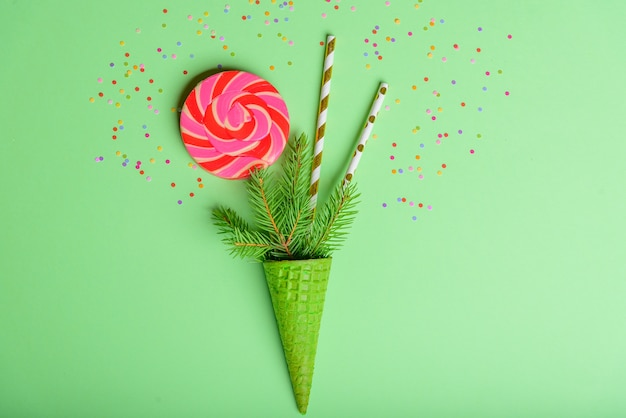New year christmas christmas holiday party celebration waffle cone, lollipops, spruce branch, copy space, green color paper background.