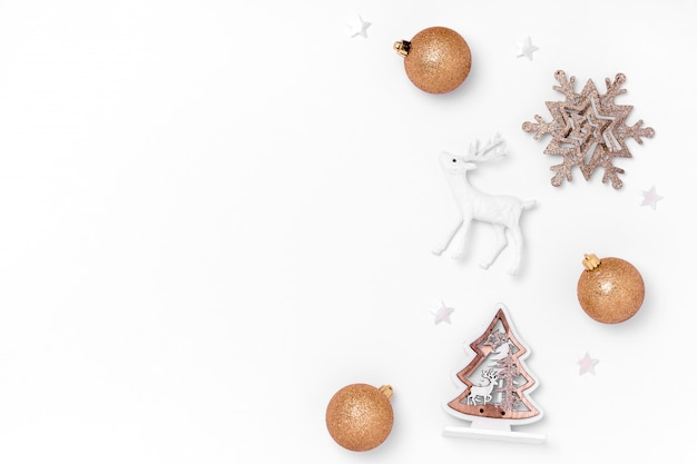 New year and christmas composition. frame frome golden and white christmas toys on white paper background. top view, flat lay, copy space