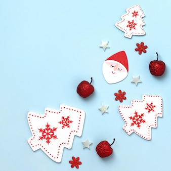 New year and christmas composition. frame frome red and white christmas toys on blue paper . top view, flat lay, copyspace,