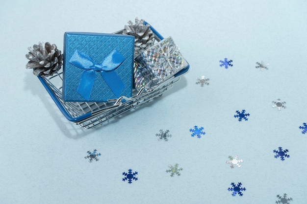 New year and christmas concept. blue gift box with a bow in a supermarket basket, silver cones, boxes and snowflakes