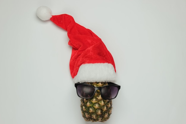New year, christmas concept. pineapple dressed in glasses with santa hat on white background. top view.