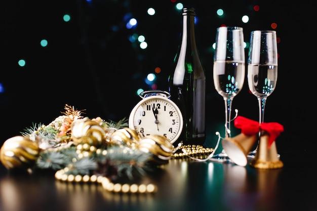 Capodanno e decorazioni natalizie. bicchieri per champagne, orologio e giocattoli per l'albero di natale