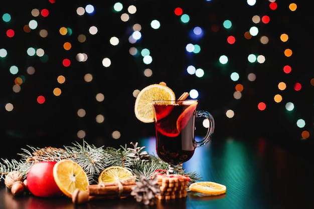 New year and christmas decor. glasses with mulled wine stand on table with oranges, apples
