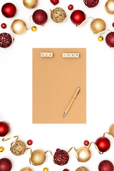 New year and christmas decorations and blank craft sheet of paper. wish list or goals concept. top view, flat lay, copy space.