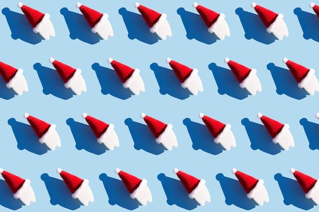 新年のクリスマスの歯科の概念。赤いサンタ帽子青い背景の歯。パターン