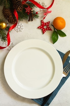 新年、クリスマスディナー、テーブルセッティング。白いコンクリートのテーブルにプレート、銀、モミの枝が付いたクリスマステーブル。上面図フラットレイ背景。スペースをコピーします。