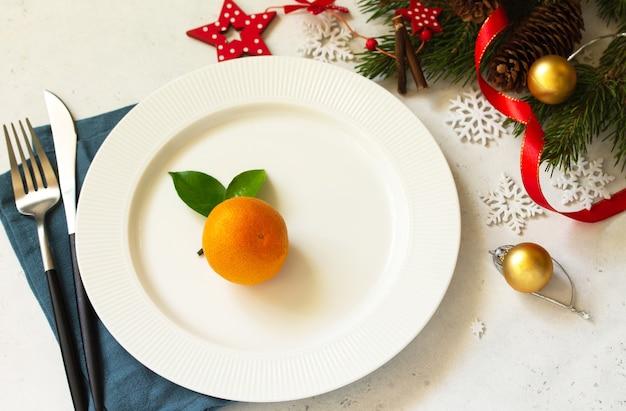 新年、クリスマスディナー、テーブルセッティング。白いコンクリートのテーブルにプレート、銀、モミの枝が付いたクリスマステーブル。
