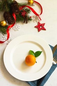 プレートシルバーとモミの枝が付いているクリスマステーブルを設定する新年のクリスマスディナーテーブル