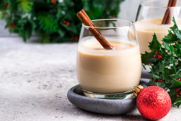 New year or christmas eggnog cocktail with cinnamon and nutmeg in a glass, branches of holly berries and ball toy on light stone , festive decoration