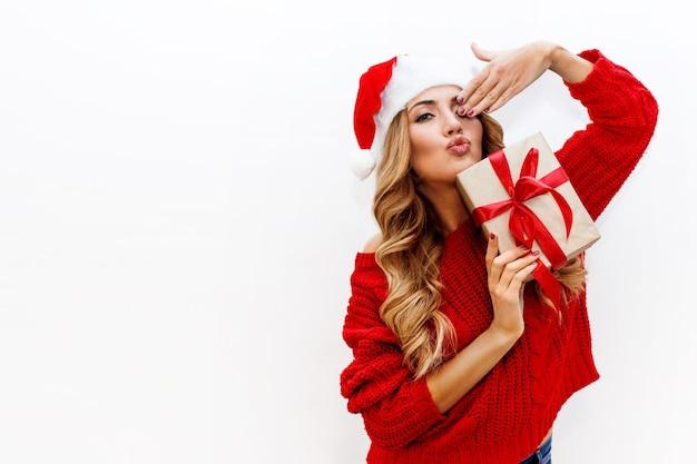 Umore del nuovo anno o della vigilia di natale. ragazza attraente bionda in cappello mascherato che tiene i contenitori di regalo isolare