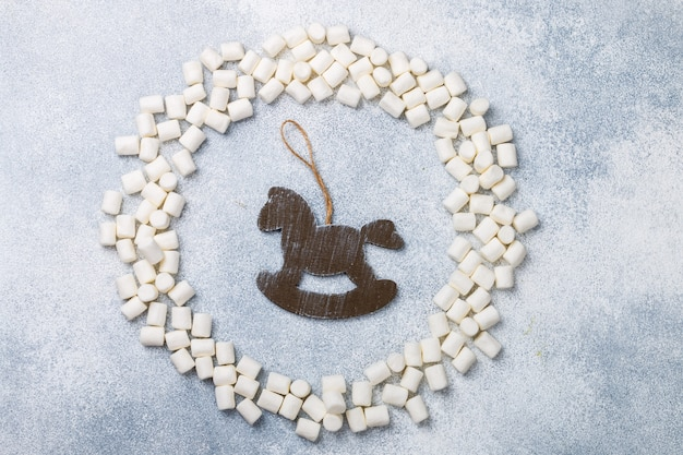 New year or christmas flat lay top view with marshmallows and rustic wooden horse toy