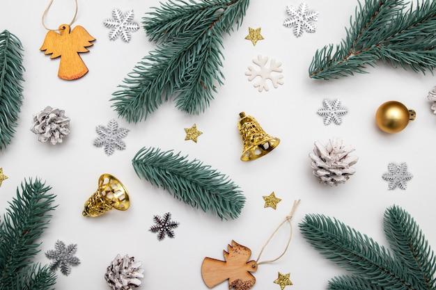 新年のクリスマスフラットは、白い背景の上にモミの枝、星、雪片、天使、お祭りの装飾で横たわっていた