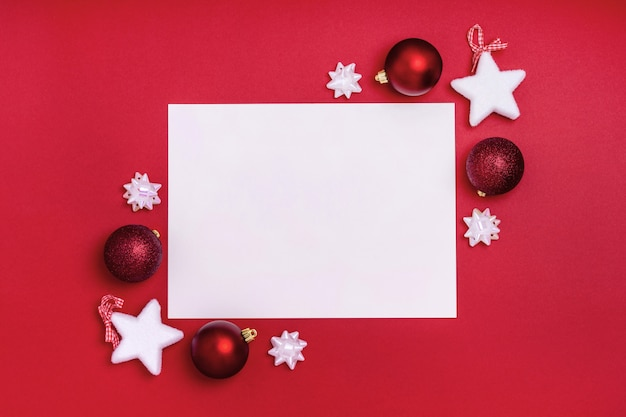 New year and christmas frame composition. blank sheet of paper with christmas decorations on red background. top view, flat lay, copy space. template design invitation card