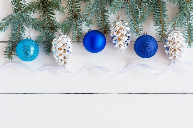 New year and christmas frame decoration with green fir tree branches and blue and silver shiny traditional baubles. greeting invitation cards on white background.