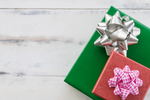 New year, christmas and holiday seasoning concept. close up of red and green gift box with beautiful ribbon on wooden plank with copy space.