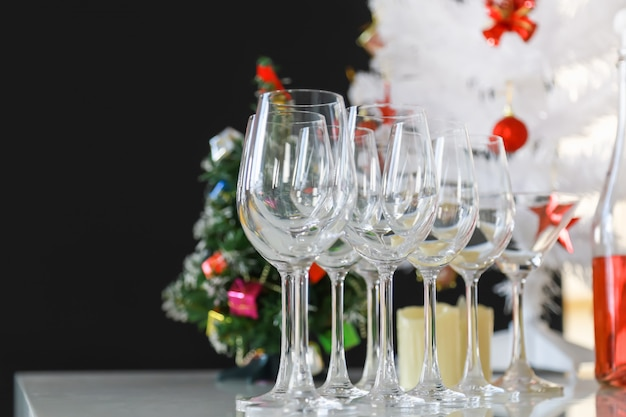 New year, christmas and holiday seasoning concept. close up of wine glass and xmas tree on table in the party