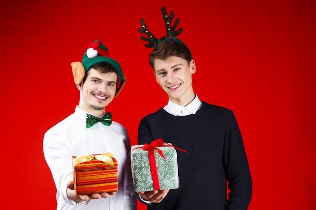 おとぎ話のカーニバル衣装エルフ耳鹿帽子を身に着けている友人カップルを笑って新年クリスマスパーティーコンセプト幸せ楽しい冬の休日を祝う現在の驚きを与える