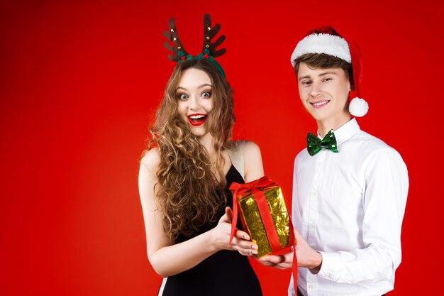 おとぎ話のカーニバル衣装サンタクロース鹿の帽子を身に着けている友人カップルを笑って新年クリスマスパーティーコンセプト幸せな楽しみは、分離された冬の休日を祝う現在の驚きを与える