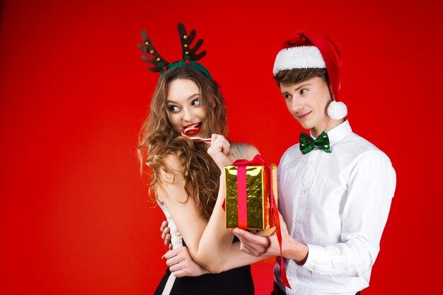 おとぎ話のカーニバル衣装サンタクロース鹿の帽子を身に着けている友人カップルを笑って新年クリスマスパーティーコンセプト幸せな楽しい冬の休日を祝うプレゼント驚きを与える